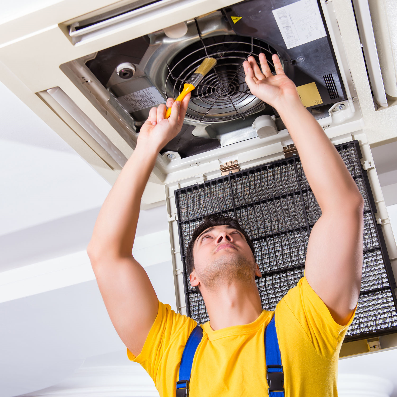 A contractor repairing an air conditioner in a ceiling