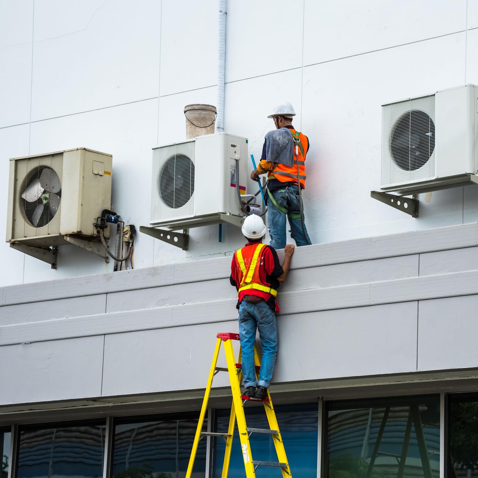 Technicians repairing an air conditioner