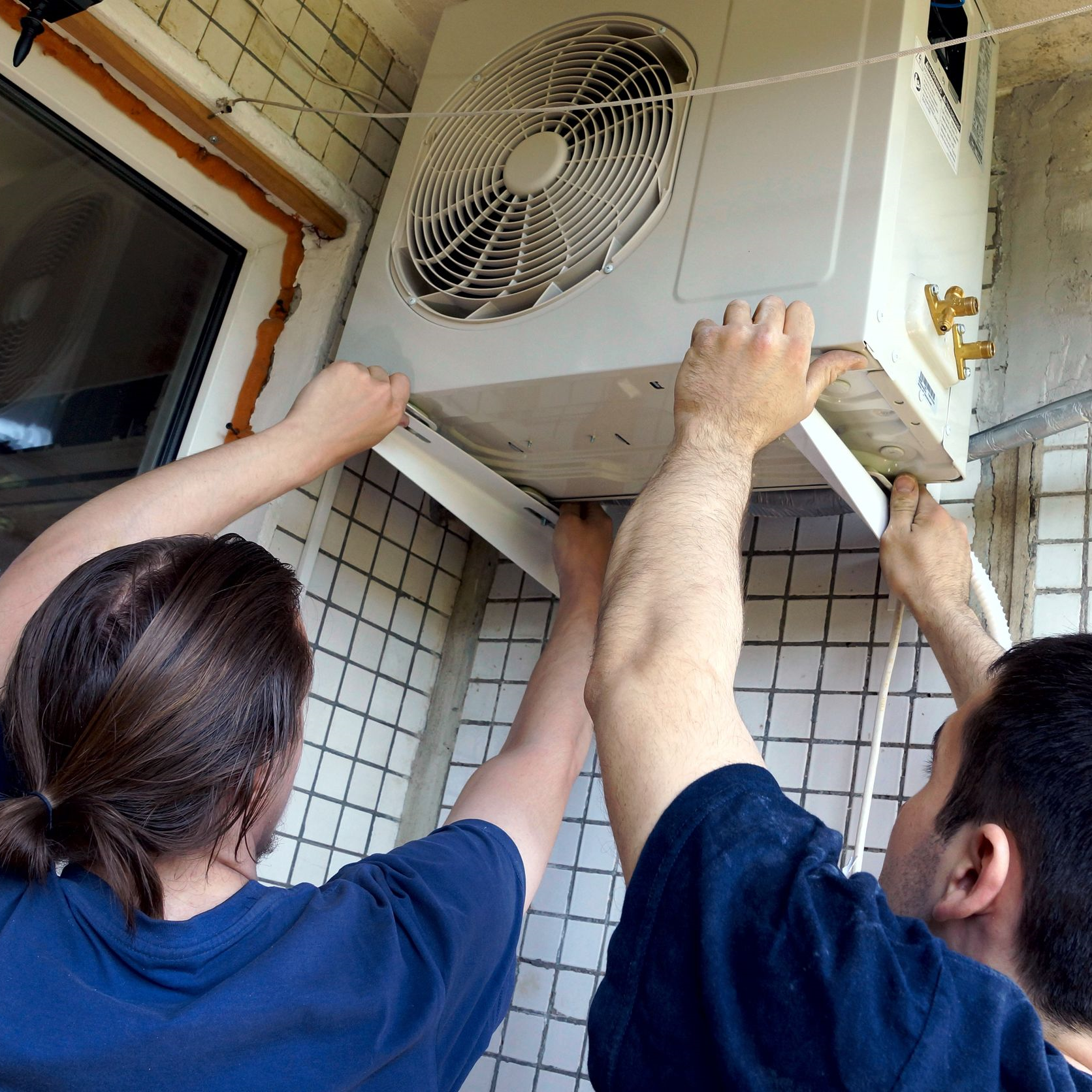 Technicians installing an air conditioner